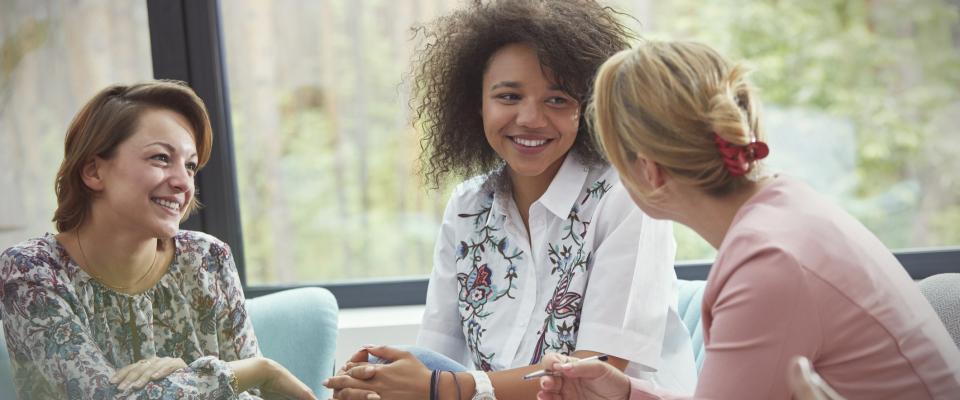 Femme animant un groupe de discussion avec deux autres femmes