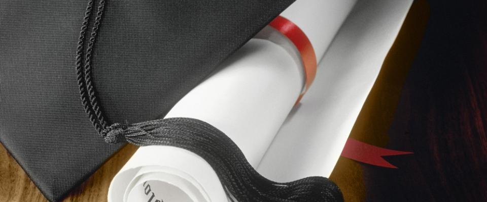 Mortier sur un diplôme enroulé d'un ruban rouge.