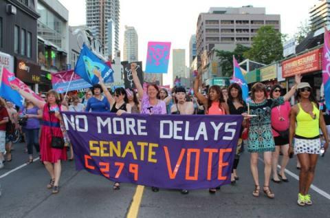 Foule colorée agitant des drapeaux et une banière critiquant les retards dans l'adoption de C-279 à la marche mondiale pour la Fierté à Toronto