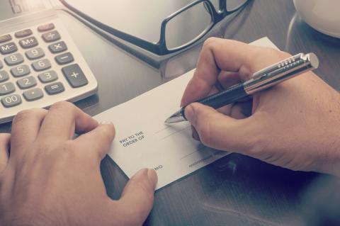 Photo d'une main qui remplit un chèque
