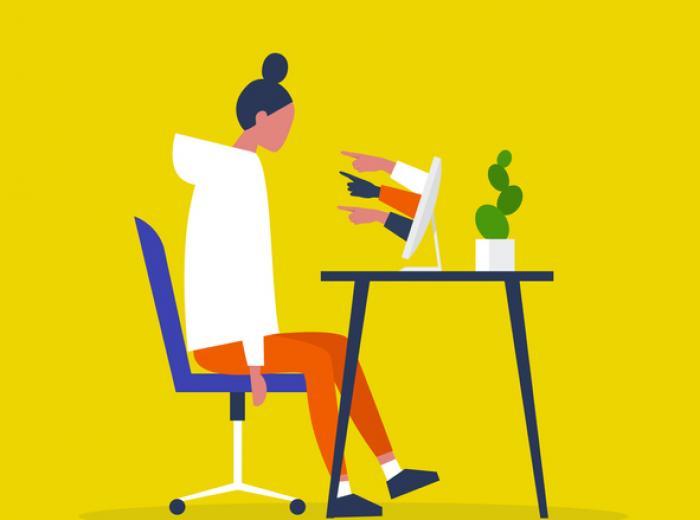 Une femme assise à un bureau. Les doigts pointent vers elle