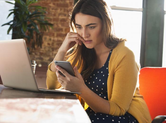 Une femme regarde son téléphone avec une expression inquiète.