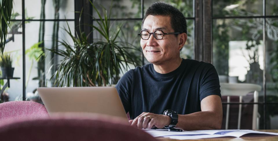 Homme d'âge avancé portant des lunettes à la maison, tapant à l'ordinateur