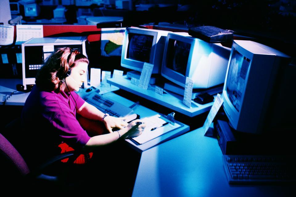 Une femme derrière des moniteurs d'ordinateur