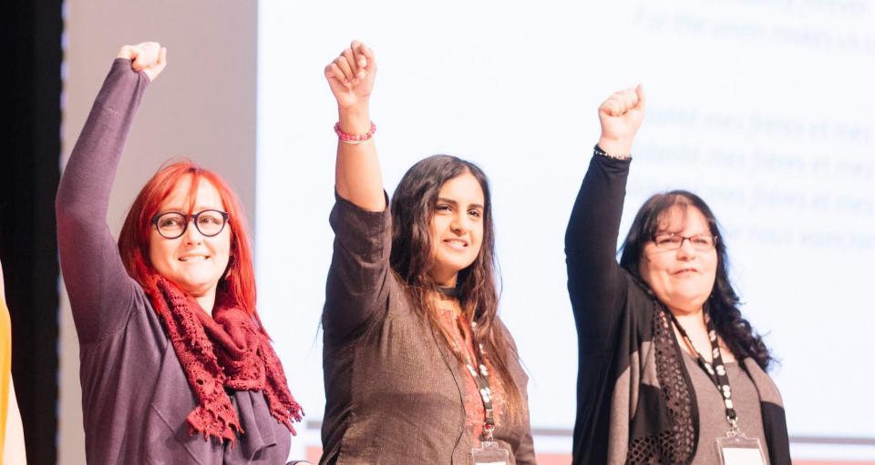 trois femmes avec les poings en l'air