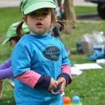 Petite fille avec couettes et chapeau vert, en t-shirt bleu portant le slogan « Votezgarderies2015 »