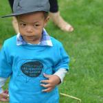 Petit garçon avec casquette de baseball et t-shirt bleu portant le slogan « Votezgarderies2015 »
