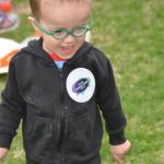 Bambin à lunettes vertes et capuchon noir, avec un autocollant portant le slogan « Votezgarderies2015 »
