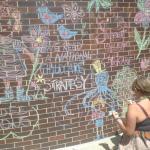 Femme dessinant une murale à la craie sur un mur de briques