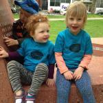 Deux petites filles assises dehors, en t-shirt bleu portant le slogan « Votezgarderies2015 »