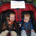 Petits jumeaux dans une double poussette avec une affiche portant l'inscription « Les garderies abordables, un enjeu pour les élections. « Votezgarderies2015 »